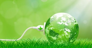 Green energy concept with Planet Earth and electric plug on lush grass